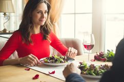 Young couple having romantic dinner in the restaurant eating salad calm close-up. Young men and women having romantic dinner in the restaurant eating salad calm Royalty Free Stock Image