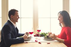Young couple having romantic dinner in the restaurant eating salad communication. Young men and women having romantic dinner in the restaurant eating salad Royalty Free Stock Image