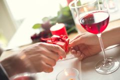 Young couple having romantic dinner in the restaurant gift close-up. Young men and women having romantic dinner in the restaurant giving a present small box Stock Images