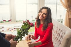 Young couple having romantic dinner in the restaurant giving flowers. Young men giving flowers to a women having romantic dinner in the restaurant smiling Stock Images