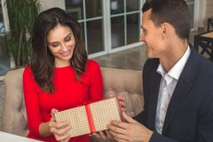 Young couple having romantic dinner in the restaurant holding a present box. Young men and women looking down on the present box having romantic dinner in the Stock Photo