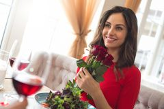 Young couple having romantic dinner in the restaurant holding roses bouquet. Young woman having romantic dinner in the restaurant holding flower bouquet smiling Royalty Free Stock Images