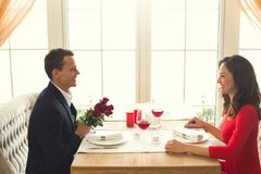 Young couple having romantic dinner in the restaurant roses bouquet. Young men and women having romantic dinner in the restaurant holding roses bouquet gift Stock Image