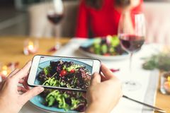 Young couple having romantic dinner in the restaurant salad photos close-up. Young men taking photos of his meal and women having romantic dinner in the Royalty Free Stock Photos