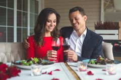 Young couple having romantic dinner in the restaurant sitting together cheers. Young men and women having romantic dinner in the restaurant sitting together Stock Images
