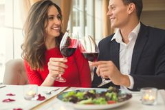 Young couple having romantic dinner in the restaurant sitting together holding wine glasses front view. Young men and women having romantic dinner in the stock image