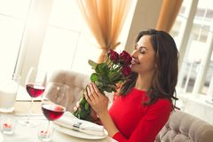 Young couple having romantic dinner in the restaurant smell the roses bouquet. Young woman having romantic dinner in the restaurant smell the roses smiling Stock Images