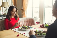 Young couple having romantic dinner in the restaurant using smartphone bored. Young men back view and women browsing smartphone bored having romantic dinner in stock images