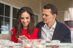 Young couple having romantic dinner in the restaurant using smartphone together. Young men and women having romantic dinner in the restaurant browsing smartphone Stock Photography