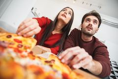 Young couple having romantic evening at home eating pizza close-up. Young men and women having romantic evening indoors eating pizza holding slices close-up Royalty Free Stock Photos