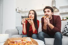 Young couple having romantic evening at home eating pizza watching tv stock images