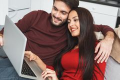 Young couple having romantic evening at home hugging watching movie Stock Photo