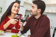 Young couple having romantic evening at home in the kitchen cheers royalty free stock photography