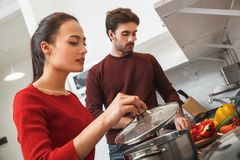 Young couple having romantic evening at home in the kitchen preparing meal together stock photo