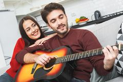 Young couple having romantic evening at home man playing song on guitar Royalty Free Stock Images