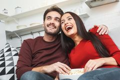 Young couple having romantic evening at home together watching comedy show Royalty Free Stock Photos