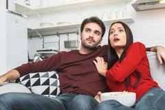 Young couple having romantic evening at home together watching mystery Stock Photography