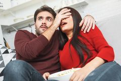 Young couple having romantic evening at home together watching scary movie Stock Photo
