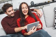 Young couple having romantic evening at home watching movies digital tablet. Young men and women having romantic evening indoors watching funny series on digital Stock Photo