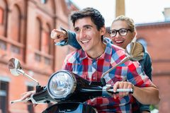Young couple having scooter ride through Berlin. Enthusiastic young couple, women and man, having scooter ride through Berlin royalty free stock photos