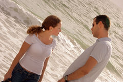 Young couple having a serious talk at that oceansi. Young couple at the beach in the gulf of mexico having a serious talk at the oceanside at that gulf of mexico Royalty Free Stock Images
