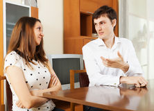 Young couple having serious talking at table Stock Photo