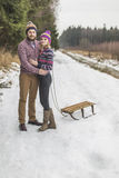 Young couple having a sled winter forest walk Stock Photography