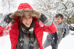 Young couple having snowball fight Stock Photo