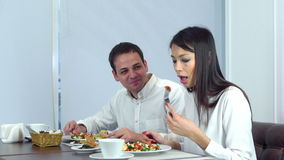 Young couple having really tasty lunch in a cafe stock footage