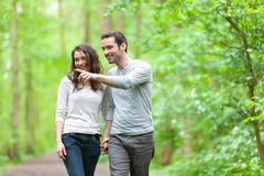 Young couple having a walk in a forest Royalty Free Stock Image