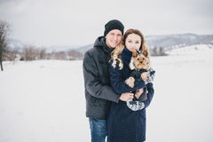 Young couple having a walk with their dog in snowy countryside Stock Image