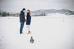 Young couple having a walk with their dog in snowy countryside. Young happy couple having a walk with their dog in winter snowy countryside Royalty Free Stock Photo