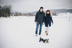 Young couple having a walk with their dog in snowy countryside Stock Images