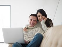 Young multi ethnic couple having wonderful time. Young couple having wonderful time in their luxury home and surfing internet Stock Image