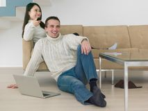 Young multi etnic couple having wonderful time. Young couple having wonderful time in their luxury home and surfing internet Stock Image