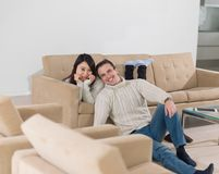 Young multi ethnic couple having wonderful time. Young couple having wonderful time in their luxury home and surfing internet Royalty Free Stock Photography