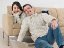 Young  multi ethnic couple having wonderful time. Young couple having wonderful time in their luxury home and surfing internet Stock Images