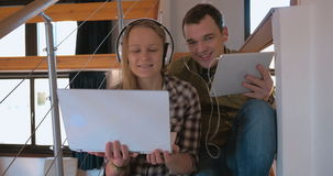 Young couple in heaphones at home enjoying music stock video footage