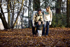 A young couple helping their son walk in the park Stock Photo