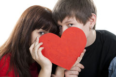 Young couple hide by red heart Royalty Free Stock Photography
