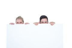 Young couple hiding behind a blank sign Royalty Free Stock Image