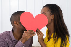 Young Couple Hiding Behind Heart Shape. Close-up Of Young African Couple Hiding Behind Heart Shape Stock Photo