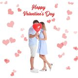 Young couple hiding behind heart-shaped air balloon on white. Celebration of Saint Valentine`s Day royalty free stock photos