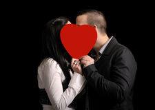Young couple hiding behind a red heartshape. Isolated on black Royalty Free Stock Images