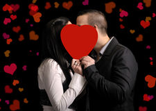 Young couple hiding behind a red heartshape Stock Image