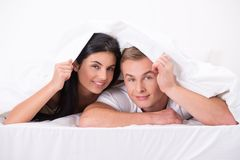 Young couple hiding under blanket Royalty Free Stock Photography