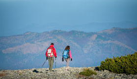 Young couple hikers with backpacks walking on rocky mountain plato Stock Photo