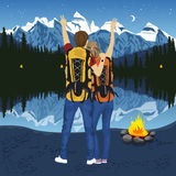 Young couple of hikers with hands up enjoying mountain lake at night near capmfire Stock Images