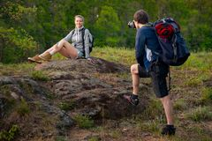 Young couple hikers resting. A man is taking photo of his girlfriend. Travel, vacation, holidays and adventure concept. Forest Mo. Young couple hikers resting. A royalty free stock image