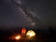 Young couple hikers resting near illuminated tent, camping in mountains at night under starry sky. Couple tourists men and women resting near tent, burning Stock Photography